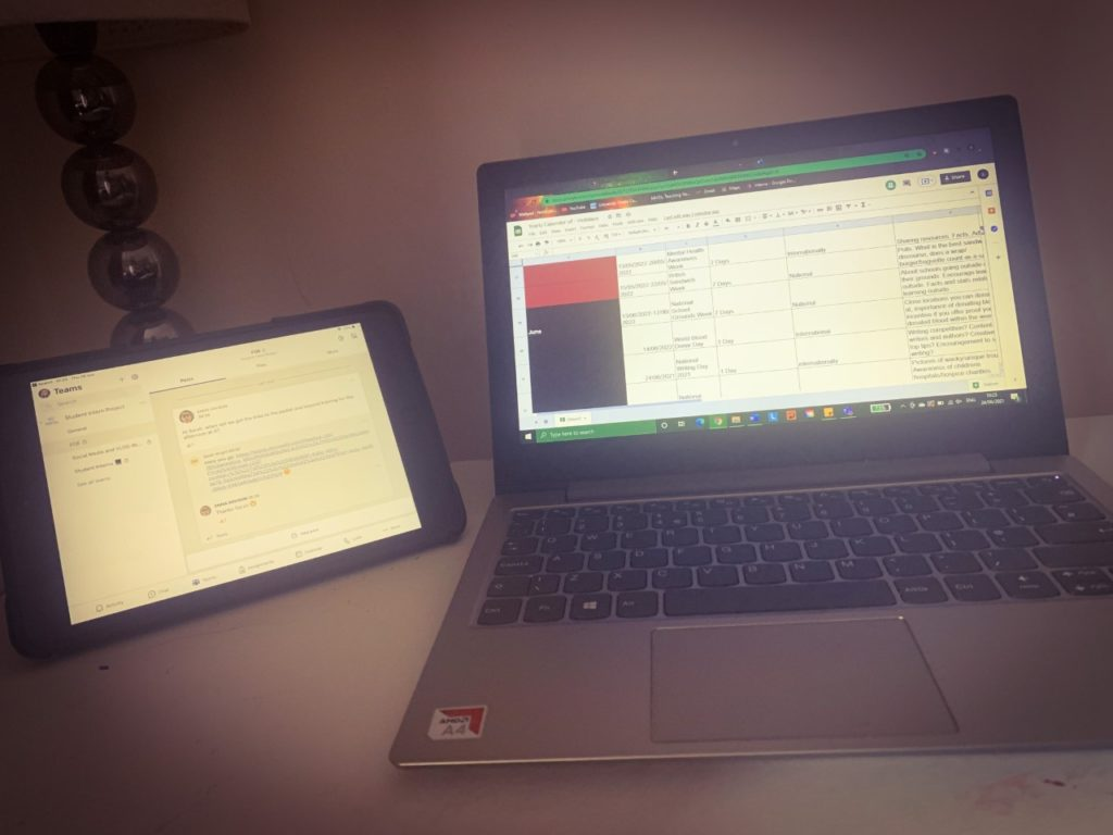 Photograph of workspace including laptop and Ipad.