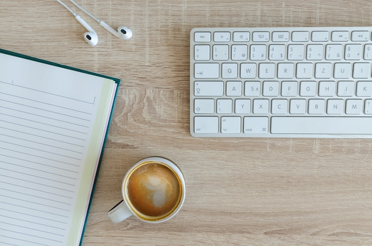 Photograph of office work desk including a keyboard, writing notebook and cup of coffee.