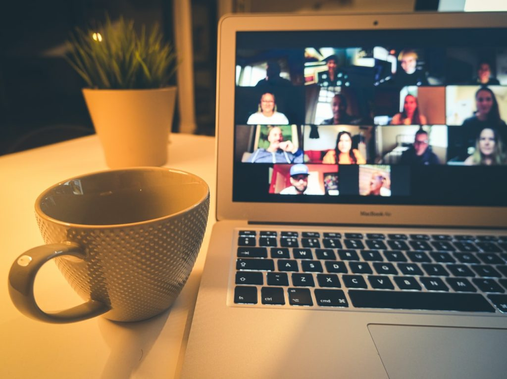 Photograph of computer with people on an online video call.