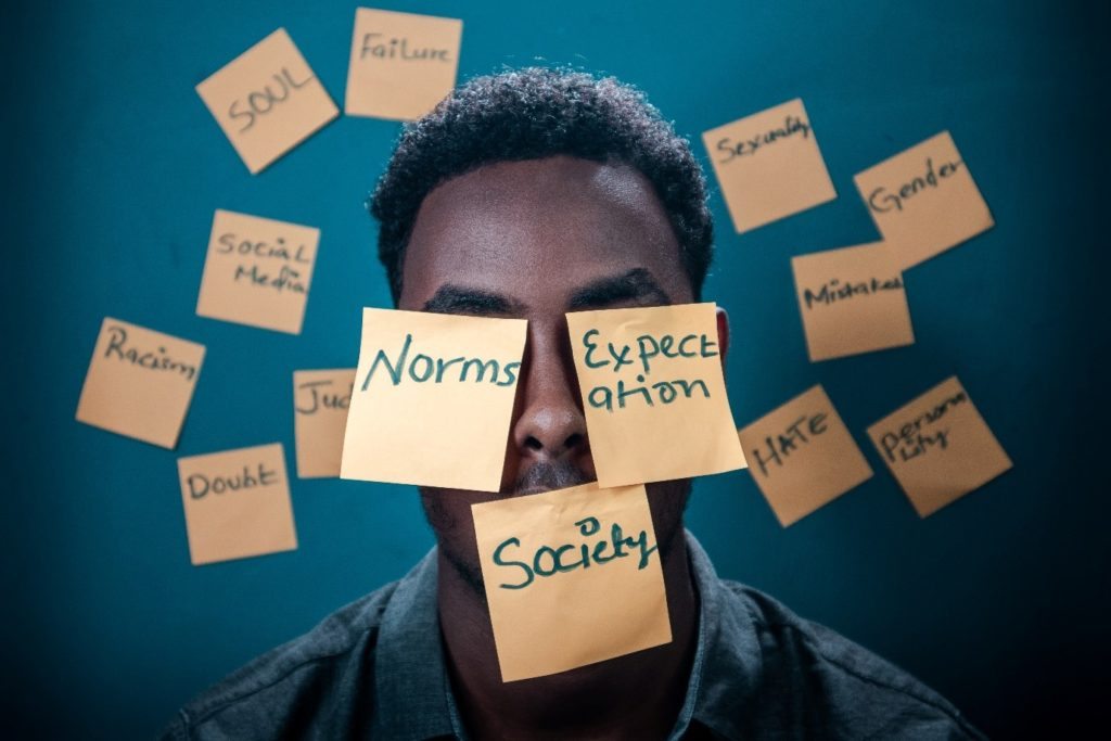 Photograph of person surround by sticky notes. Notes contain words including: norms, expectation and society.
