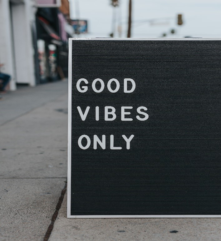 A picture containing text saying good vibes only on an outdoor sign.