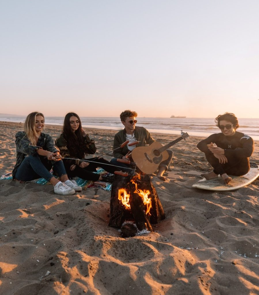 Photograph of people sitting around a campfire
