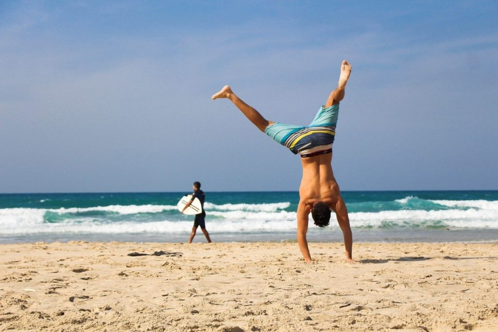 Image of a beach showing the sea, sand and sky.  A person in the background is about to surf and another is doing a handstand on the sand.