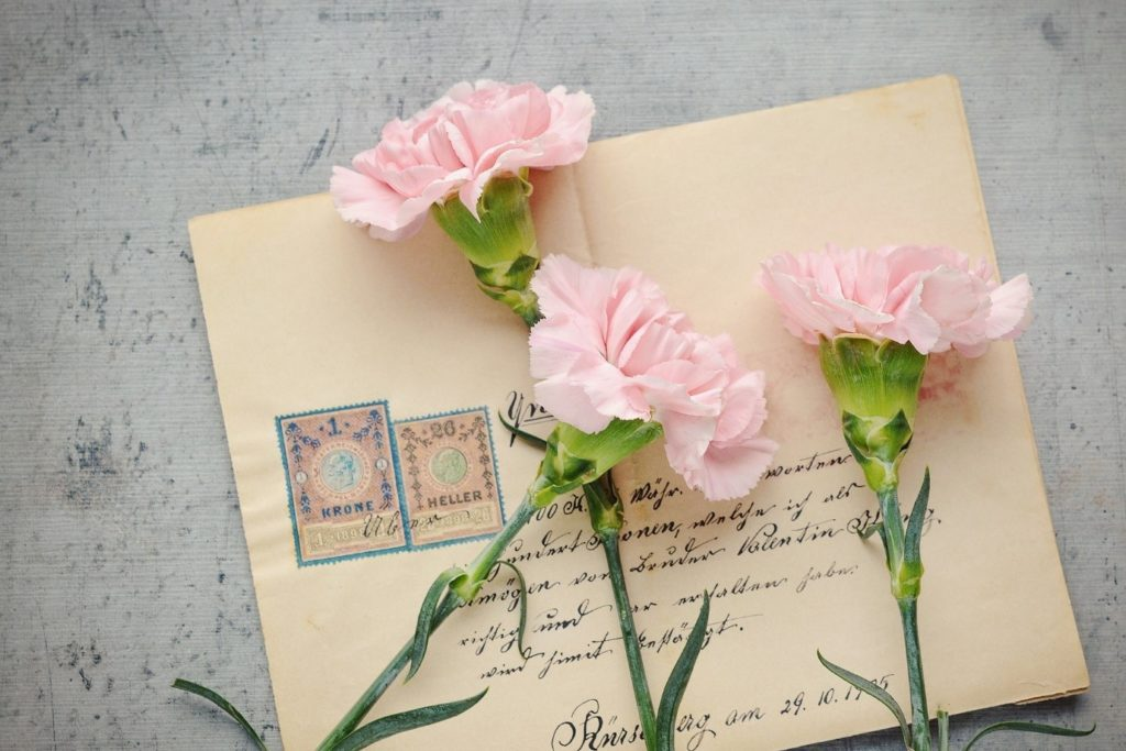 A personal letter with 3 pink roses on top.