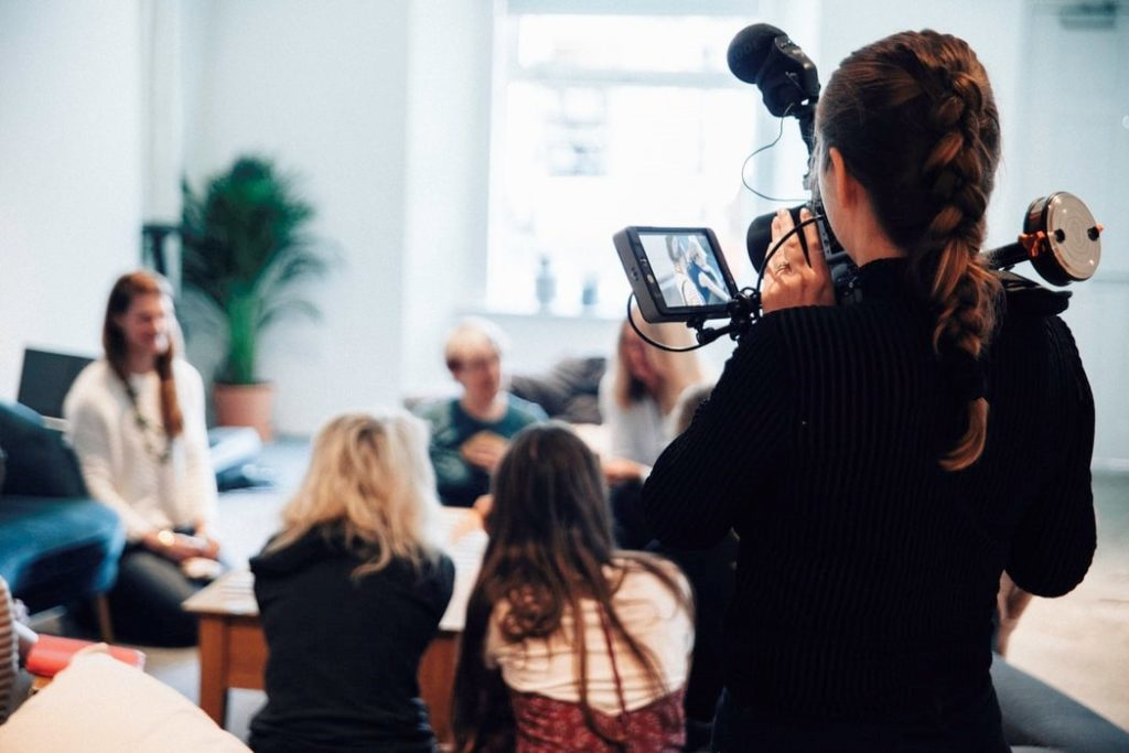 Photograph of someone recording a group a people.