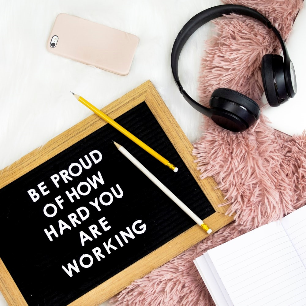 """Black wireless headphones with yellow and white pencils. Board saying """"Be proud of how hard you are working"""""""