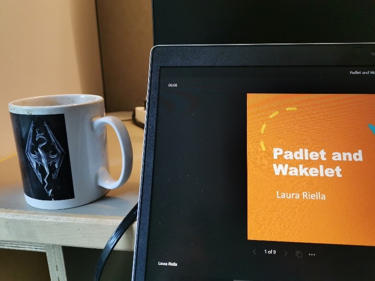 A cup of tea on a desk next to a laptop, viewing the Padlet and Wakelet training session.