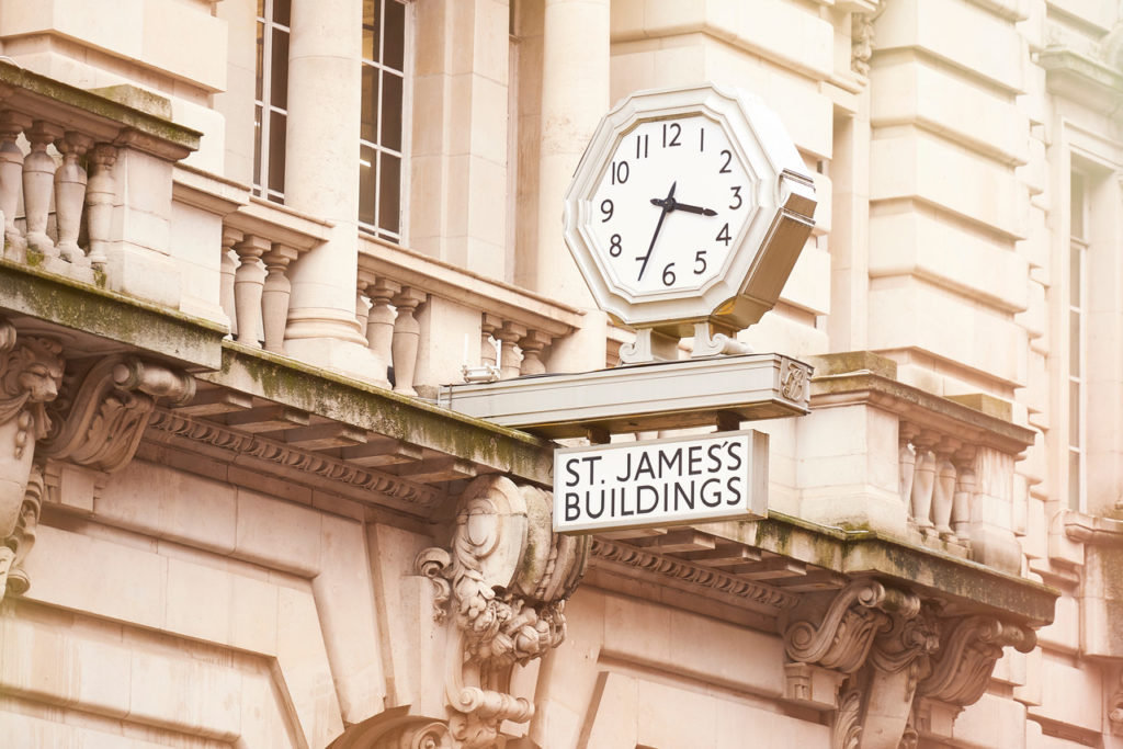 The large clock above the main door of the neo-classical entrance to the St James building.
