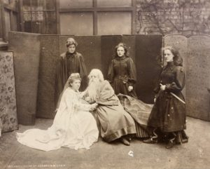 A sepia photograph featuring five female students in costume. One on the left is in a flowing white gown, crouched next to another student with a long beard. The other three students are standing and dressed in black, one in the forefront with what appears to be a fake sword.