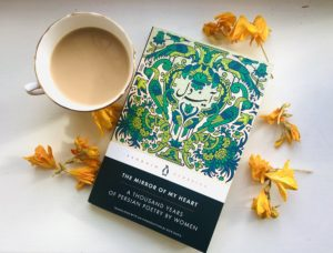 A Penguin book entitled The Mirror of My Heart: A Thousand Years of Persian Poetry by Women. A cup of tea sits next to the book and yellow flower petals surround it.