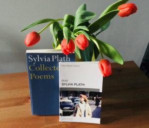Red tulips overhang from a vase, onto two Sylvia Plath books of poetry, 'Collected Poems' and 'Ariel'.