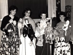 Four students in 1950s attire and standing side by side and smiling, are holding what appear to be handmade puppets on sticks.